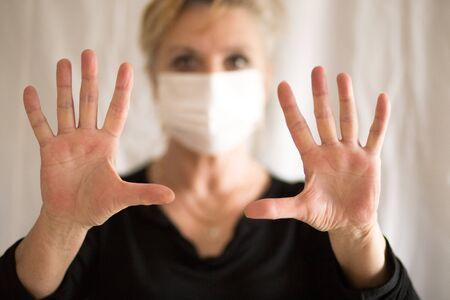 Senior woman wearing mask, shows clean hands and show stop hands gesture for stop corona virus outbreak. Coronavirus and epidemic virus symptoms.