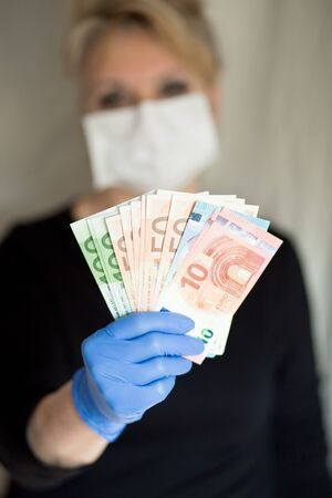 Senior woman wearing mask holds cash Euro notes in a hand in gloves. Selective focus.