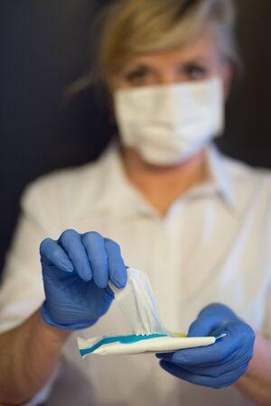 Senior woman wearing mask, gloves takes out a wet cloth. Selective focus. Coronavirus and epidemic virus symptoms. Фото со стока