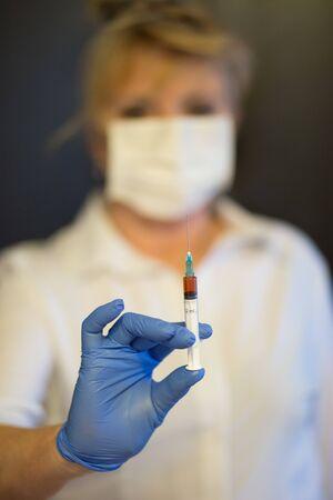 Senior woman wearing mask, gloves holds a syringe in hand. Selective focus. Coronavirus and epidemic virus symptoms.