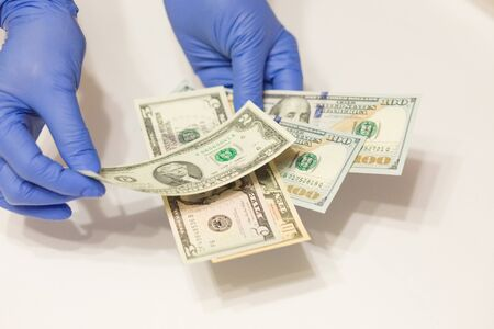 hands wearing medical gloves counting dollar banknotes on white background Фото со стока
