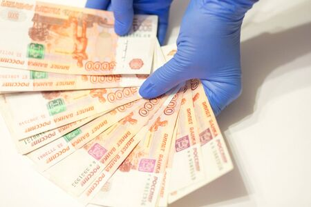 hands wearing medical gloves counting roubles banknotes on white background