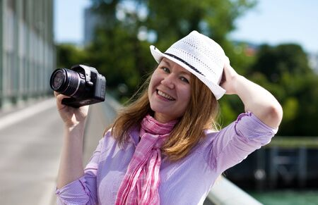 blond cheerful  woman with a photocamera and cowboys hat photo