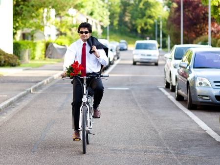 Businessman is riding a bicycle in a suit coming after work with bouquet of red roses Stock Photo