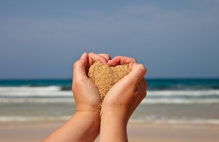 heart in sand: Hands holding a sand with a heart towards sea