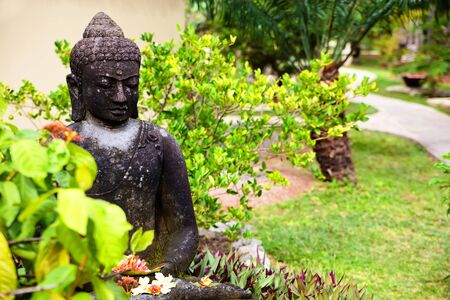 budda: Statue of Buddha holding flowers in a garden Stock Photo