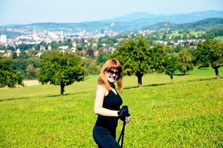 hiils: Woman doing Nordic walking in the field with city view at background Stock Photo