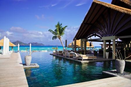 seychelles: 세이셸에있는 고급 호텔에있는 티키 오두막에 수영장과 라운지에서 영역을 수영 스톡 사진