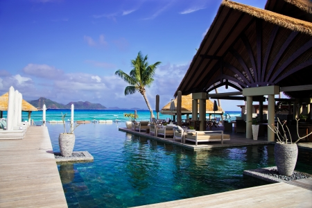 hut: swimming pool and loung area with tiki hut in luxury hotel in seychelles