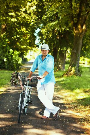 Romantic, handsome man standing with bicycle in the park