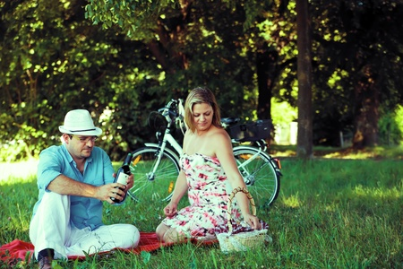 open country: Middle aged couple having picnic, man opening wine Stock Photo