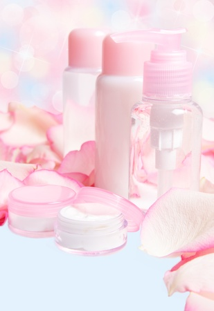 cream, lotion and gel in pink container with rose petals on a blurred background  photo