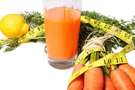 Carrot juice with bunch of carrots, waist measurement and lemon, diet concept photo