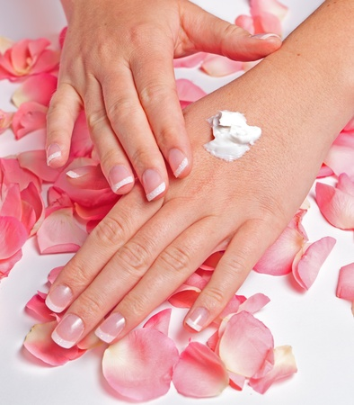 Beautiful hands with french manicure applying cream on rose petals