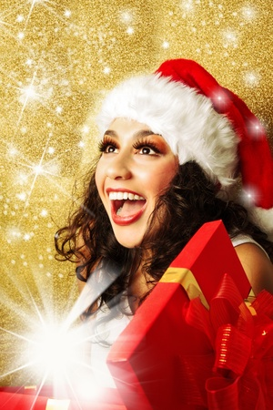 Delighted, beautiful, happy woman with gift box in santa claus hat photo