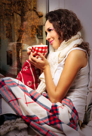 woman with cup of coffee or tea watching out of window photo