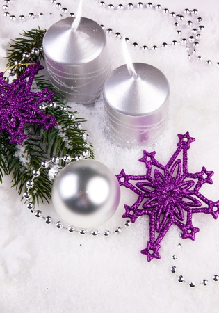 christmas decoration - violet stars with silver candles and bauble on a white snow Stock Photo