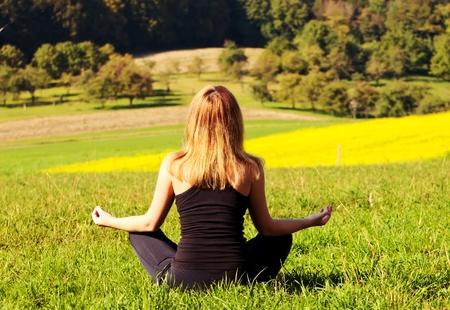 mujer meditando: la mujer en el emplazamiento de loto y meditar en el campo floreciendo Foto de archivo