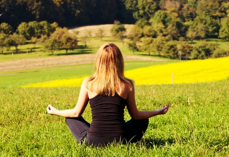 woman siting in lotus and meditating at the blooming field photo