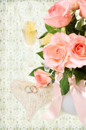 rings on a heart with bouquet of pink roses and champagne photo