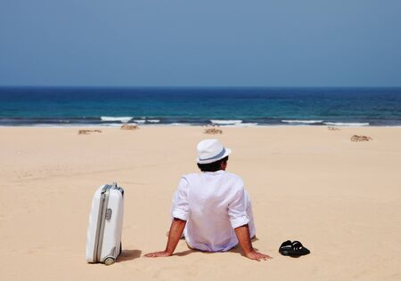 siting: Man siting with luggage on a sand and observing sea