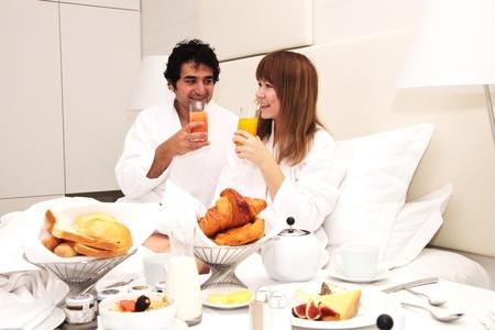 honeymooners: Feliz pareja joven con desayuno en la cama, bebiendo jugo de naranja