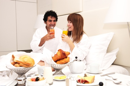 Young happy couple having breakfast in bed, drinking orange juice Stock Photo