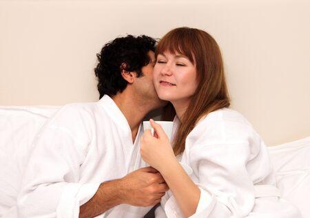 honeymooners: Loving couple having tea or coffee in a bed, kissing and huging