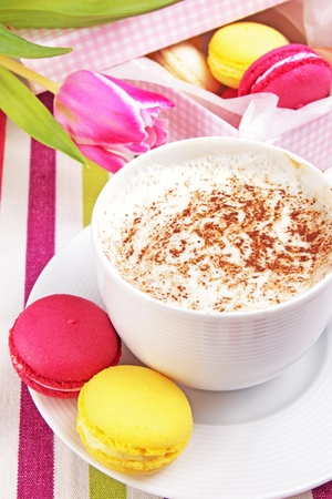 Fresh cup of cappucino with colorful macaroons and tulip photo