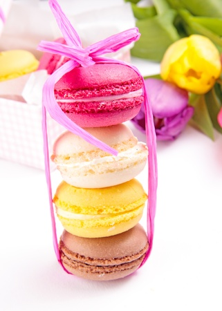 Colorful macaroons with tulips on a background
