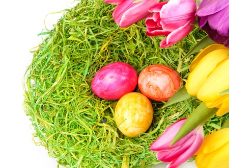 Three colorful eggs in a nest with tulips, Easter boder Stock Photo - 11808843