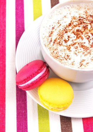 Colorful macaroons with a cup of coffee or cappucccino  photo