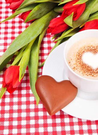 Valentines day - cup of coffee or cappuccino with chocolates heart and red tulips on a background photo