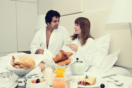honeymooners: Feliz pareja joven con desayuno en la cama, comiendo medialunas