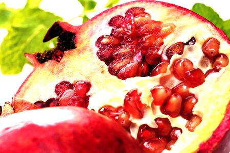 half of pomegranate with green leaves, fresh cut photo