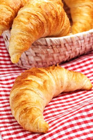 Baked croissants in rustic breadbasket with red cell napkin Stock Photo - 13346079