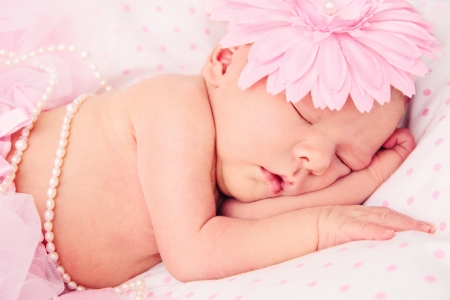 tightly: Adorable, sweet ballerina with fluffy pink skirt and flower sleeping tightly