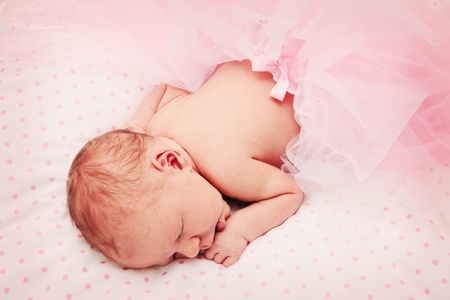 Adorable, sweet ballerina with fluffy pink skirt sleeping comfortable photo