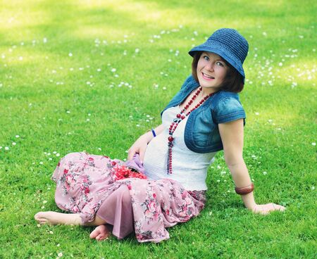 Cute pregnant romantic woman sitting on a grass with bouquet of roses photo