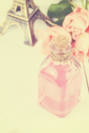 color therapy: Rose essential oil, perfume with bouquet of pink roses and Eiffel Tower