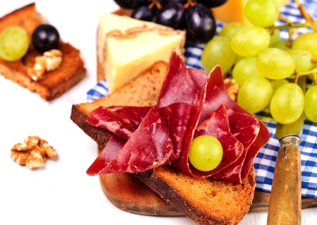 Sandwich with b�ndnerfleisch - dried beef  with variety of cheese and grapes on a cutting board photo