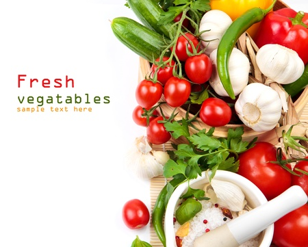 Ingredients for salad, fresh vegetables - cherry tomatoes, cucumbers, garlic and herbs on a white background with copy space Stock Photo