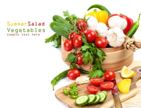 Cooking salad, fresh vegetables - cherry tomatoes, cucumbers, garlic and herbs on a white background with copy space photo