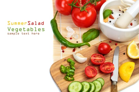 Cooking salad, sliced fresh vegetables - cherry tomatoes, cucumbers, garlic and herbs on a white background with copy space photo
