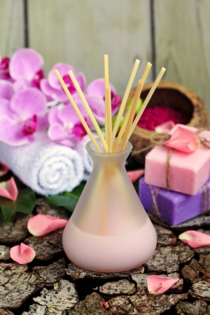 Aroma diffuser with bath setting - towels, soap and orchid flower over wood Stock Photo