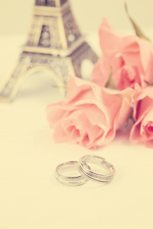 two rings with Eiffel Tower and bouquet of pink roses at background