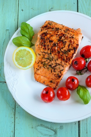cooked fish: Grilles fish with cherry tomatoes and lemon over wooden background