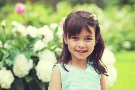 Adorable, cheerful chinese girl in the garden with blooming roses photo