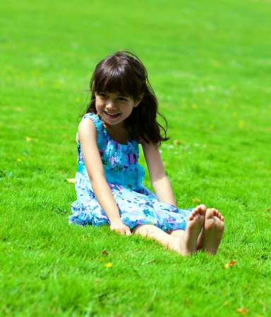 little girl barefoot: Portrait of little chinese girl sitting on a grass in the park Stock Photo