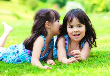 Two little girls lying on a grass in the park and telling a secret